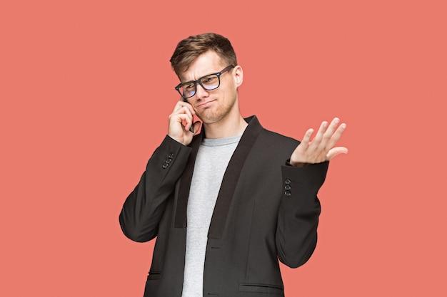 El joven empresario caucásico sobre fondo rojo hablando por teléfono celular