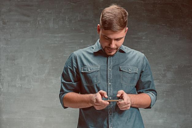 El joven empresario caucásico sonriente en espacio gris con teléfono