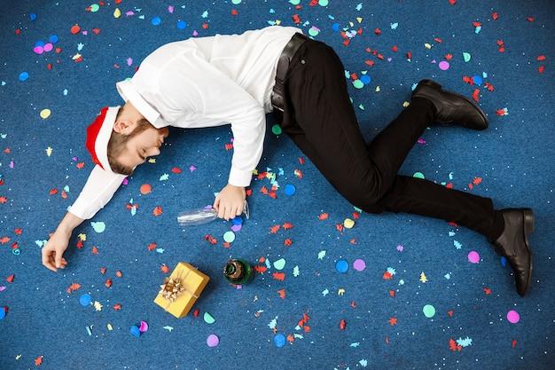 Joven empresario celebrando la navidad en la oficina durmiendo en el piso.