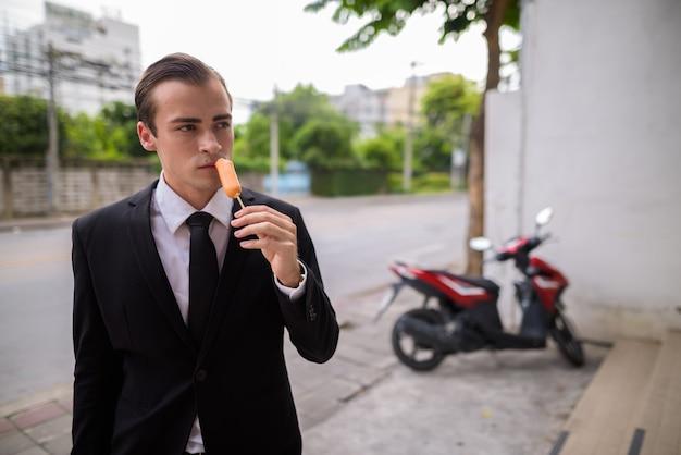 Joven empresario comiendo salchichas de hot dog al aire libre