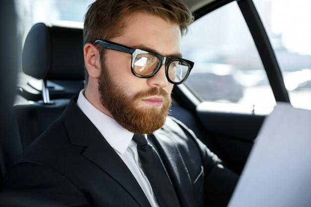 Joven empresario concentrado analizando documentos mientras viaja
