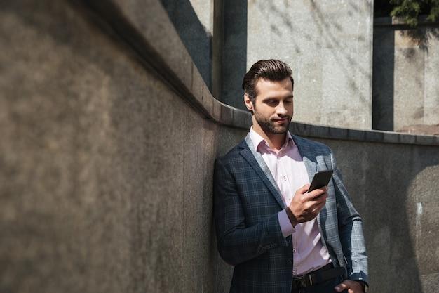 Joven empresario concentrado chateando por teléfono.
