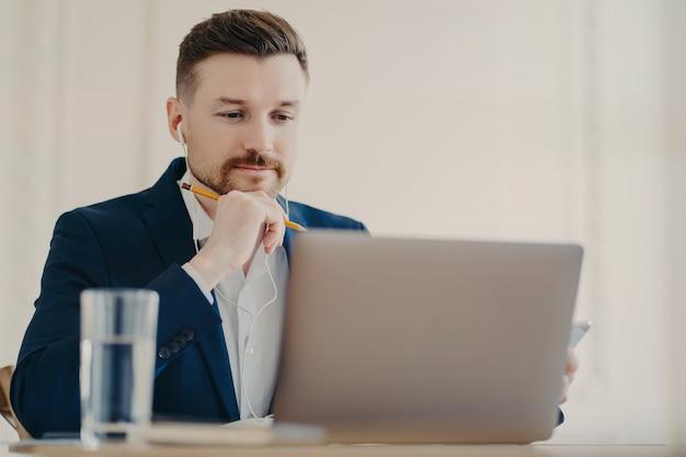 Joven empresario concentrado o emprendedor con auriculares, sosteniendo un lápiz y mirando la pantalla del portátil moderno mientras ve un seminario web de negocios en línea trabajando en el escritorio en la oficina de luz