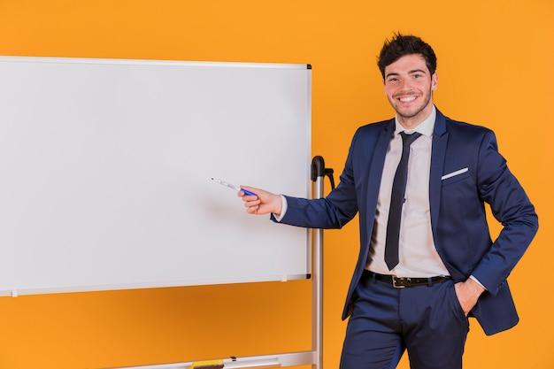 Joven empresario dando presentación contra un telón de fondo naranja
