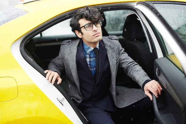 Joven empresario dejando taxi bajo la lluvia