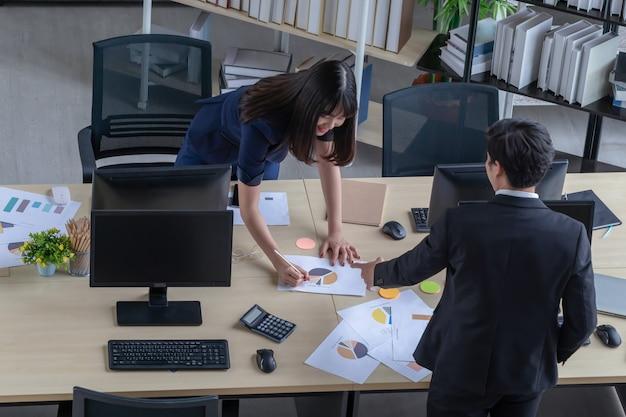 Un joven empresario describe el trabajo de una bella mujer asiática con un traje azul oscuro en el escritorio de una oficina moderna.