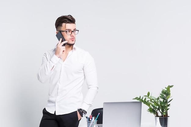 Joven empresario elegante en camisa blanca hablando con alguien por su teléfono en la pared moderna blanca