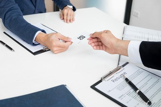 Joven empresario en la entrevista de contratación en la oficina, reunión en el vestíbulo de la oficina, cambiando las tarjetas de visita