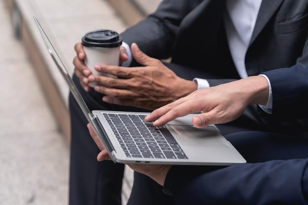 Joven empresario está escribiendo los resultados de rendimiento empresarial en el teclado de la computadora portátil
