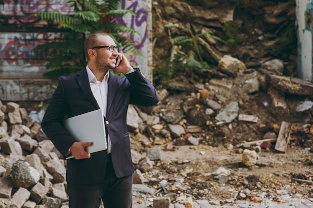 Joven empresario de éxito en camisa blanca, traje clásico, gafas. hombre de pie con ordenador portátil, hablando por teléfono cerca de ruinas, escombros, edificio de piedra al aire libre. oficina móvil, concepto de negocio.