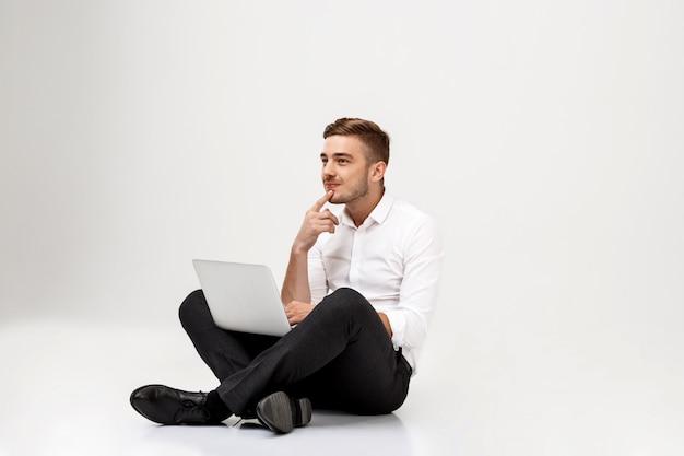 Joven empresario exitoso pensando, sentado con el portátil.