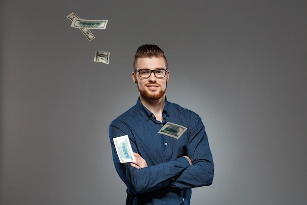 Joven empresario exitoso posando entre caer dinero sobre la pared oscura.