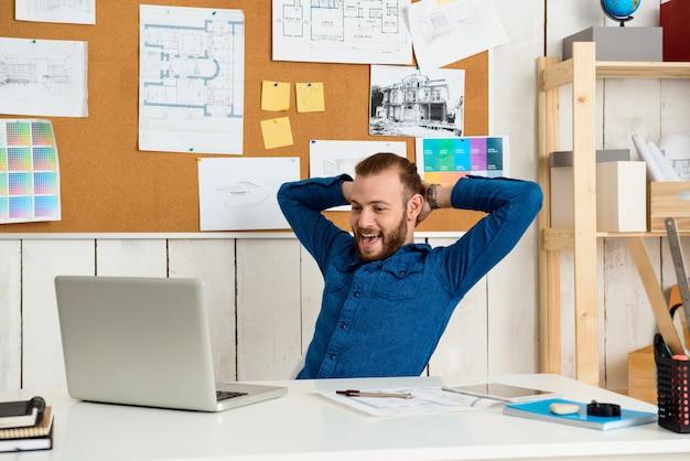 Joven empresario exitoso regocijo, sentado en el lugar de trabajo con ordenador portátil