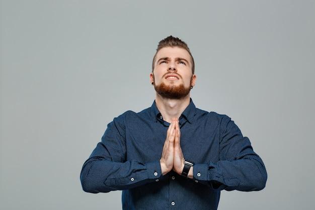 Joven empresario exitoso rezando sobre la pared gris.