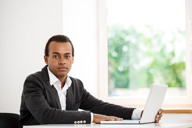 Joven empresario exitoso sentado en el lugar de trabajo con ordenador portátil