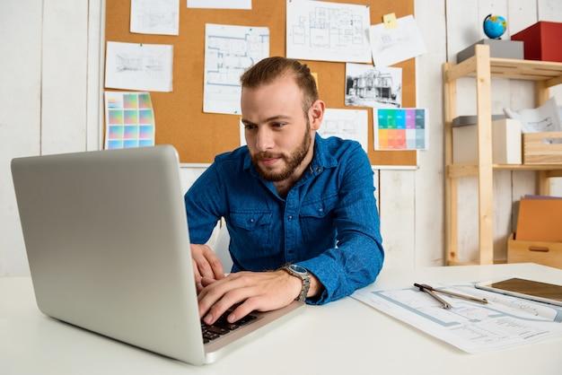 Joven empresario exitoso sonriendo, sentado en el lugar de trabajo escribiendo en la computadora portátil
