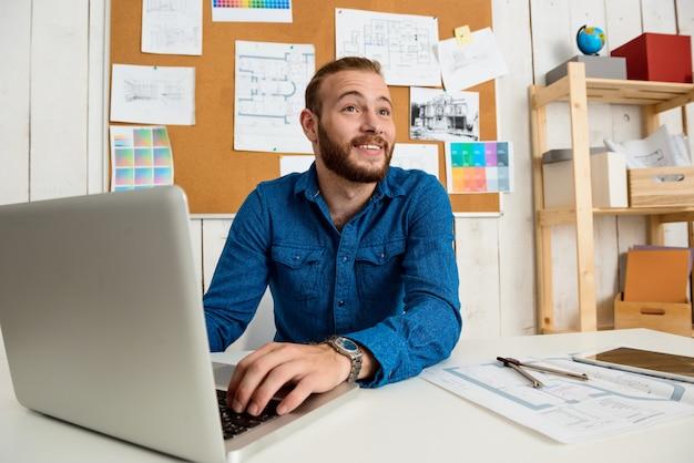 Joven empresario exitoso sonriendo, sentado en el lugar de trabajo con ordenador portátil