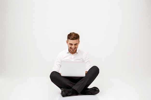 Joven empresario exitoso sonriendo, sentado con el portátil.