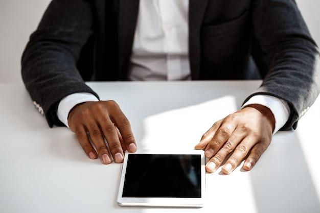 Joven empresario exitoso con tableta, sentado en el lugar de trabajo