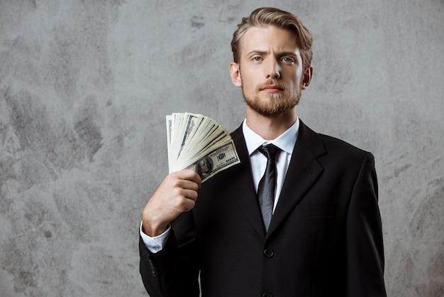 Joven empresario exitoso en traje con dinero