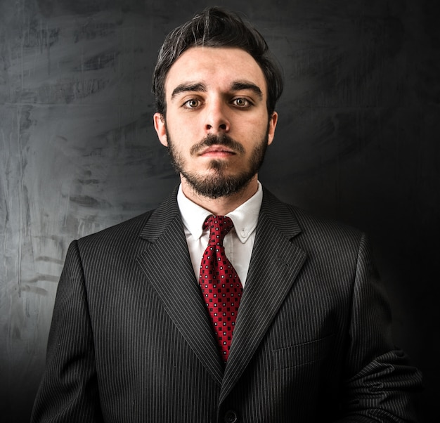 Joven empresario en fondo oscuro