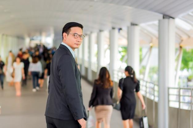 Joven empresario guapo de asia con sus gafas de pie en la pasarela de la ciudad moderna.