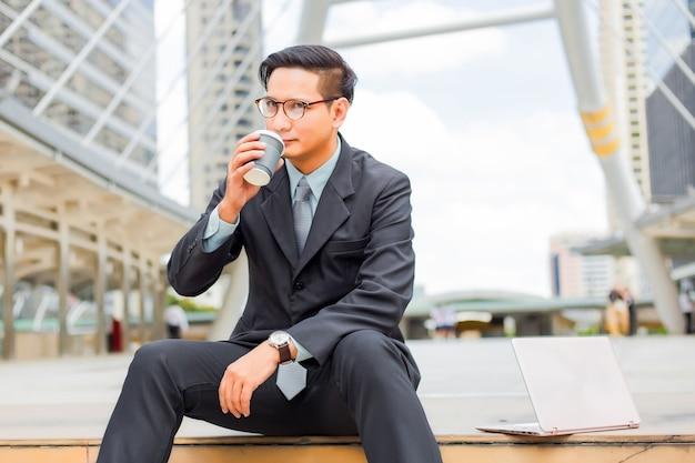 Joven empresario guapo asiático bebiendo café caliente en la ciudad moderna.