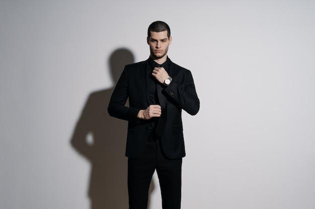 Joven empresario guapo en camisa negra y traje negro