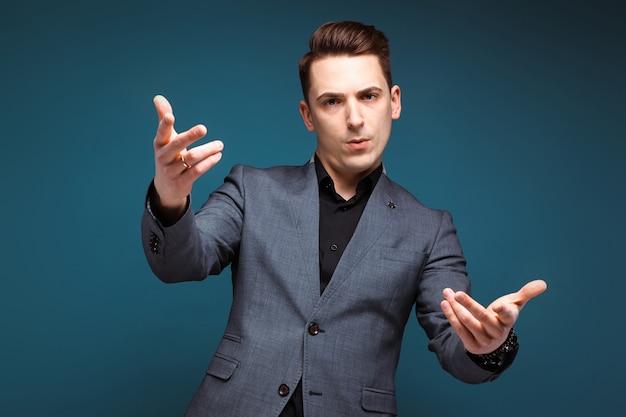 Joven empresario guapo en chaqueta gris y camisa negra
