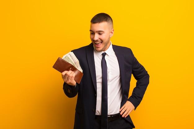 Joven empresario guapo contra el concepto de dinero de pared plana
