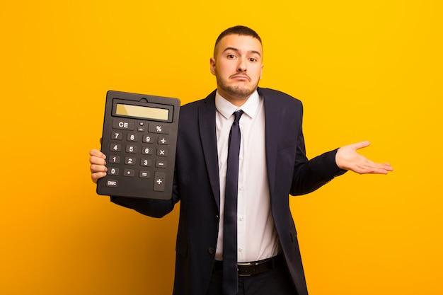 Joven empresario guapo contra el fondo plano con una calculadora