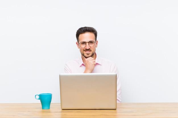 Joven empresario guapo mirando feliz y sonriente con la mano en la barbilla, preguntándose o haciendo una pregunta, comparando opciones