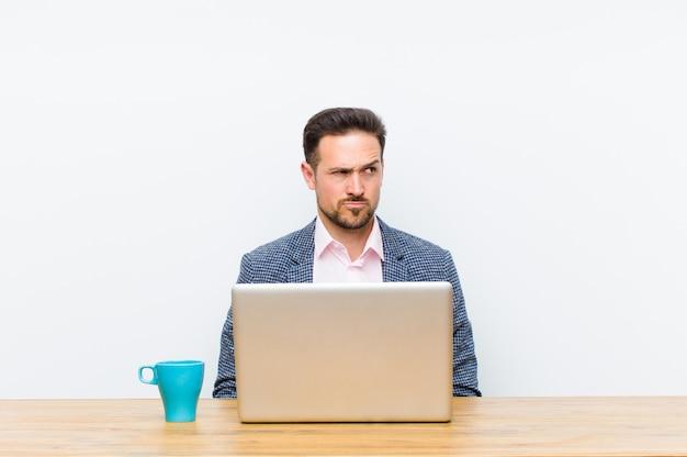 Joven empresario guapo mirando perplejo y confundido, preguntándose o tratando de resolver un problema o pensando