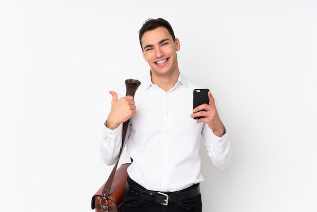 Joven empresario guapo en pared aislada con pulgares arriba gesto y sonriendo
