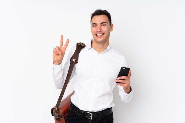 Joven empresario guapo en la pared que muestra el signo de la victoria con ambas manos