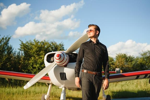 Joven empresario guapo de pie cerca de avión privado