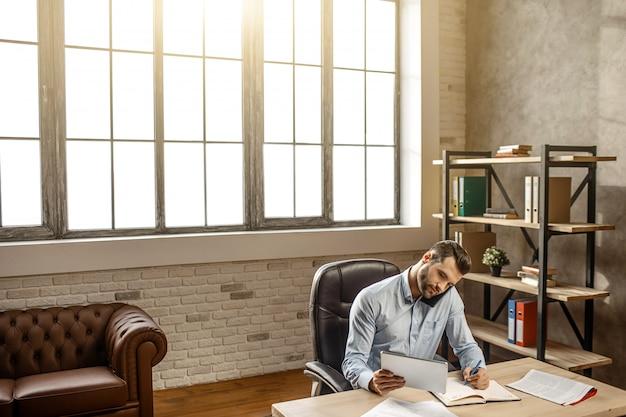 Joven empresario guapo sentarse a la mesa y escribir en su propia oficina. habla por teléfono y mira la tableta en la mano. ocupado y concentrado. plática de negocios. encuentro en línea.
