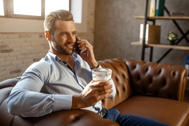 Joven empresario guapo sentarse en el sofá y hablar en su propia oficina. sostiene un vaso de whisky en la mano y sonríe. segura y sexy. feliz y alegre