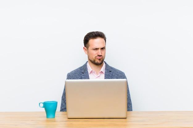 Joven empresario guapo sintiéndose confundido y dudoso, preguntándose o tratando de elegir o tomar una decisión