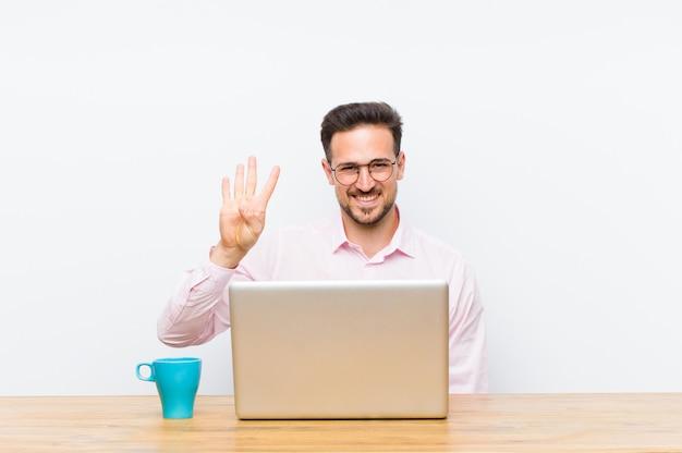 Joven empresario guapo sonriendo y mirando amigable, mostrando el número cuatro o cuarto con la mano hacia adelante, cuenta atrás
