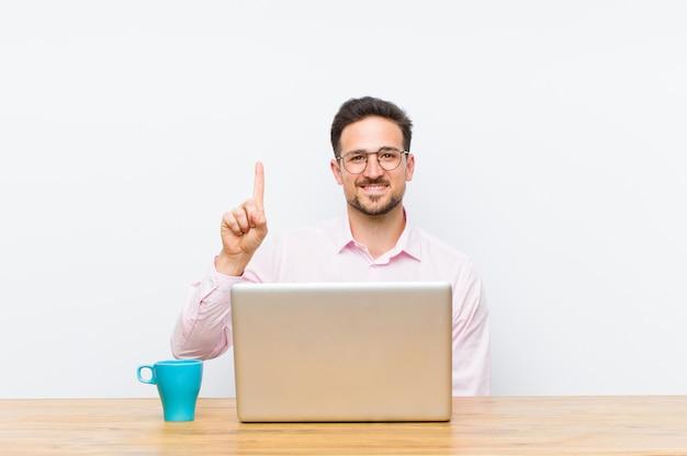 Joven empresario guapo sonriendo y mirando amigable, mostrando el número uno o primero con la mano hacia adelante, contando hacia atrás
