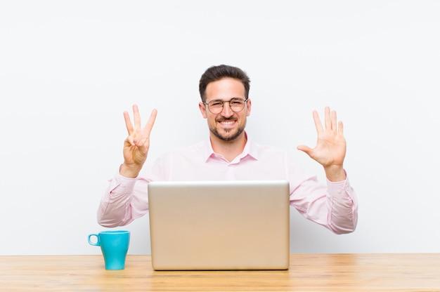 Joven empresario guapo sonriendo y mirando amigable, mostrando el número ocho u octavo con la mano hacia adelante, cuenta atrás