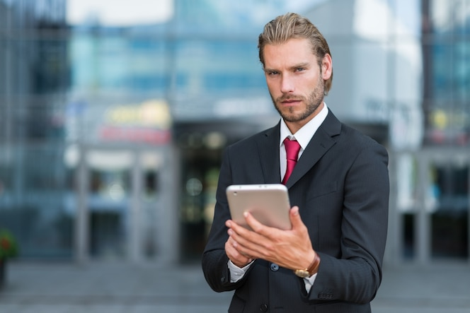 Joven empresario guapo usando su tableta