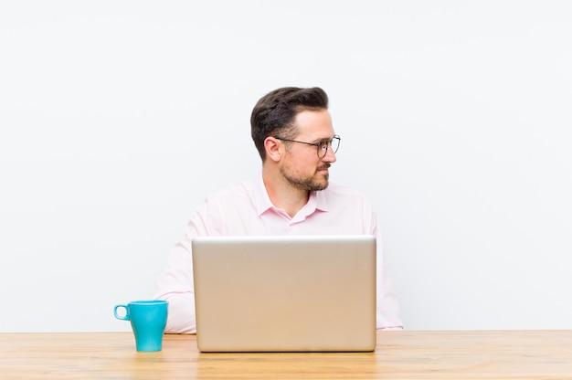 Joven empresario guapo en la vista de perfil que busca copiar espacio por delante, pensando, imaginando o soñando despierto