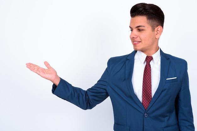 Joven empresario guapo vistiendo traje azul sobre blanco