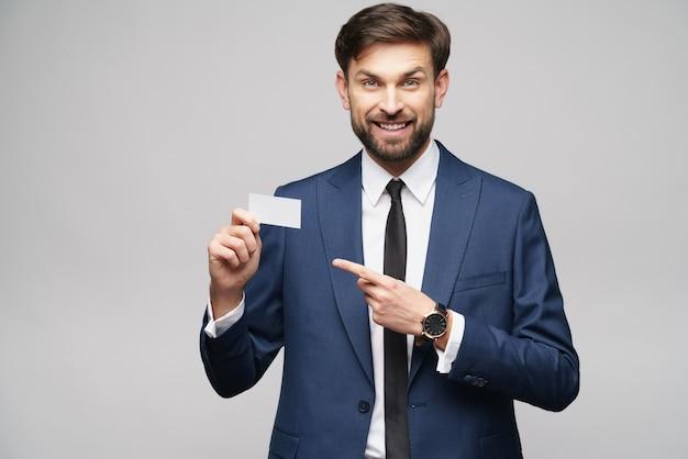 Joven empresario guapo vistiendo traje con tarjeta de visita