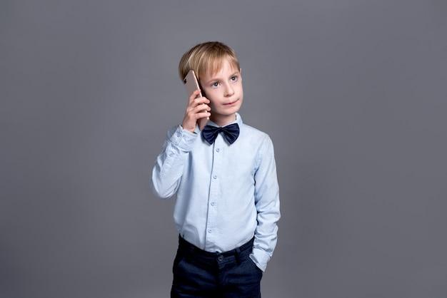 Joven empresario hablando por teléfono. niño pequeño que presenta en un gris