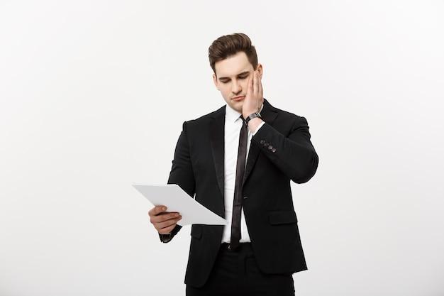 Joven empresario hansome con un documento en sus manos aislado sobre fondo blanco.