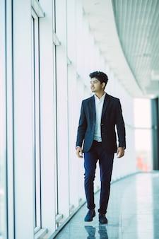Joven empresario indio asiático caminando a la oficina en la mañana