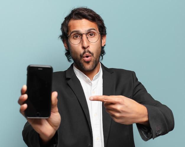 Joven empresario indio guapo mostrando su pantalla vacía de teléfono